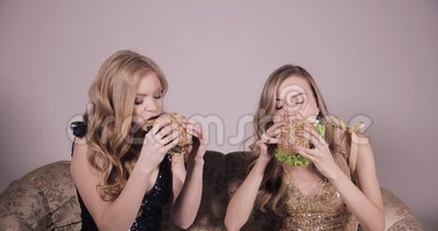 Two girlfriends eating hamburgers. Two women eating very tasty burgers. Two girlfriends eating hamburgers outdoors stock footage