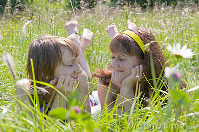Two girlfriends lie on a grass and talk