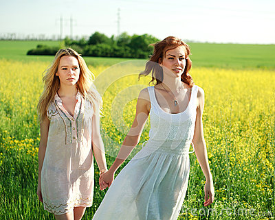 Two girlfriends in long dresses, together outdoors