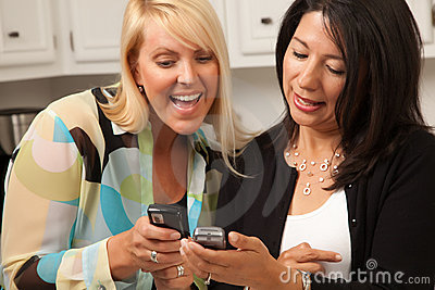 Two Girlfriends Sharing with Their Cell Phones