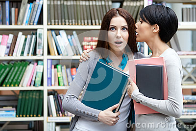 Two girlfriends whisper at the library