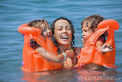 Two girls bathing in lifejackets with young woman