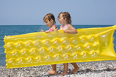 Two girls bearing in hands inflatable mattress