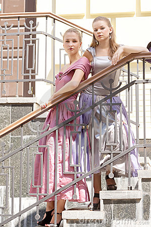 Two girls in beautiful dresses on the stairs
