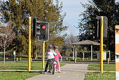 Two girls on bikes at stop light