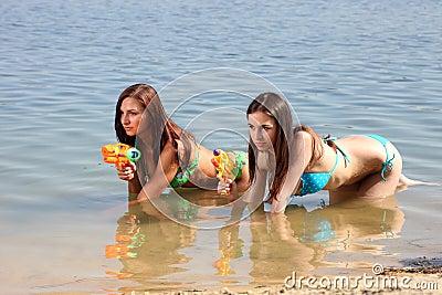 Two girls in bikini play with a water guns