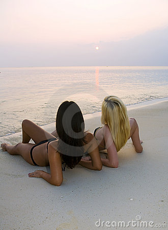 Two girls in bikinis at the beach at sunrise