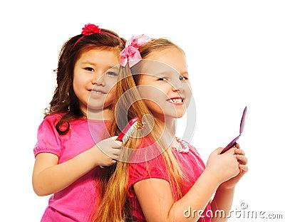 Two girls brushing hair