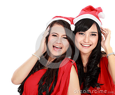 Two girls in christmas santa hat have fun