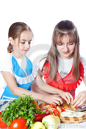 Two girls of the cook prepare a vegetarian dish