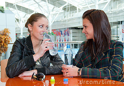 Two girls drink water in food court in a mall