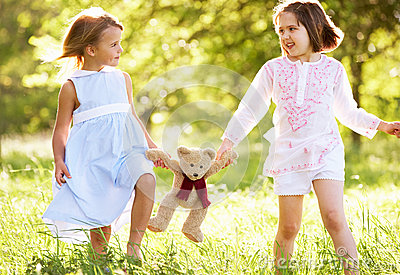 Two Girls In Field Carrying Teddy Bear