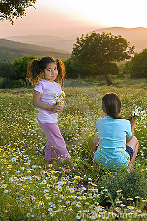Two girls flowers field at sunset