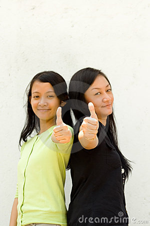 Two girls give thumbs up
