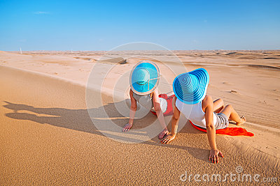 Two girls in hats relaxing in the desert