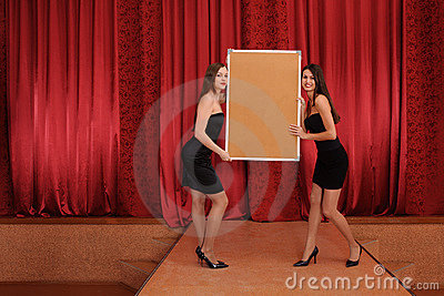 Two girls hold empty board