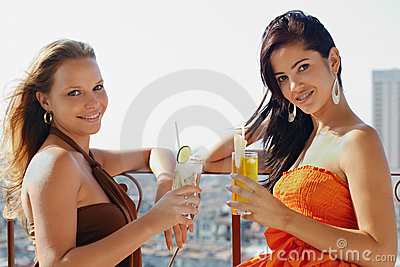 Two girls on holidays in Cuba, holding cocktails