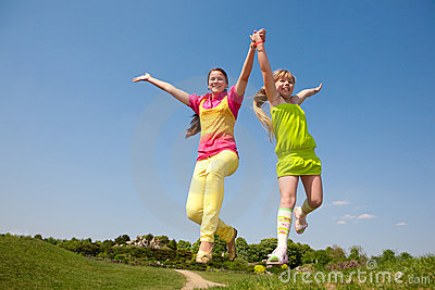 Two Girls Jumping On Green Meadow Stock Images - Image: 9887534