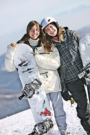 Two girls keeping snowboards