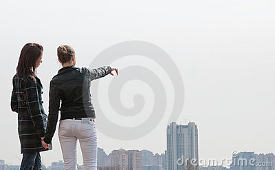 Two girls looking to a city panorama