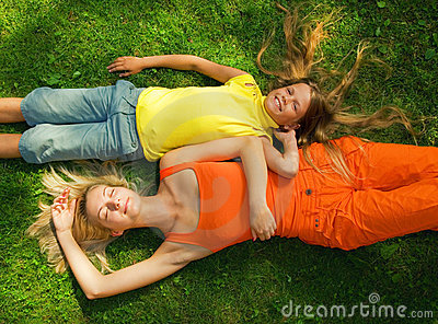 Two girls lying on a meadow