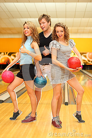 Two girls and man hold balls in bowling club