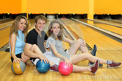 Two girls and man sit on floor in bowling club