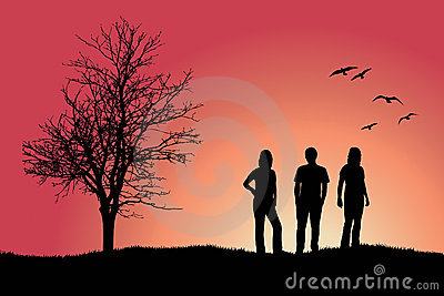 Two girls and man standing near bare tree