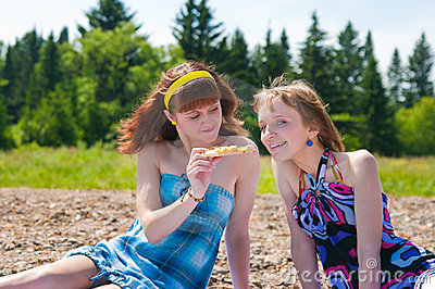 Two girls on a meadow eat a pizza