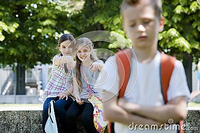 Two girls mocking a boy
