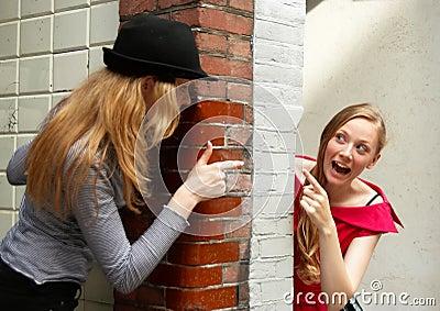 Two girls peeking around the w