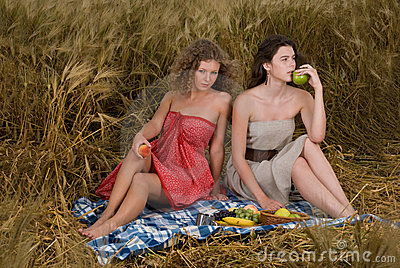 Two girls on picnic in wheat field