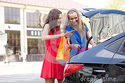 Two girls are piling the bags in the car