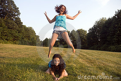 Two girls play leap frog