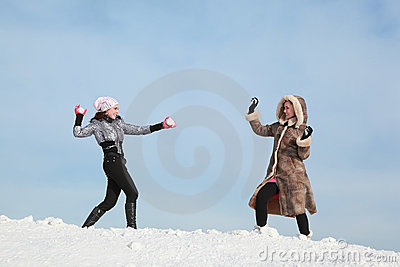 Two girls play snowballs and laugh