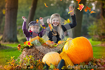 Two girls playing with autumn leaves