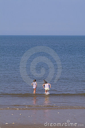 Two girls playing in waves