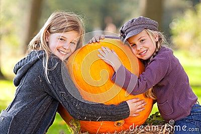 Two girls proud of their big pumpkin