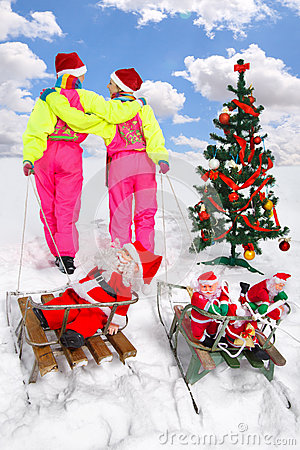 Two girls pulling Santos on a sled