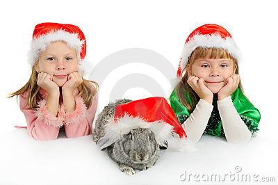 Two girls with a rabbit in red caps of Santy