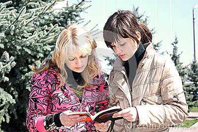 Two girls read the book in a park