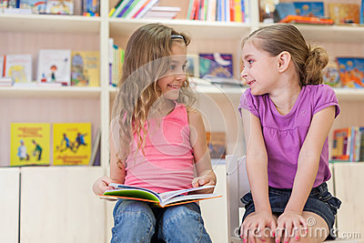 Two girls reading a book in the library and laugh