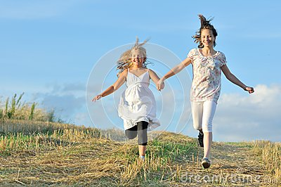 Two girls running across the field