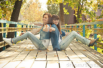 Two girls showing thumbs-up