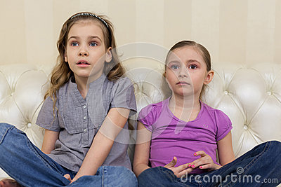 Two girls sitting on a sofa and watching TV intently