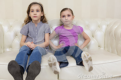 Two girls sitting on a sofaand watching TV