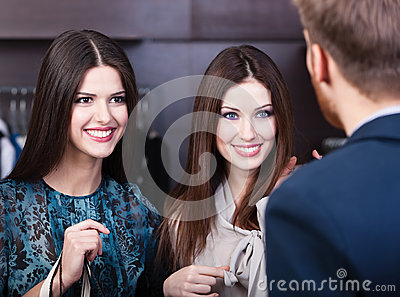 Two girls smiles at shop assistant