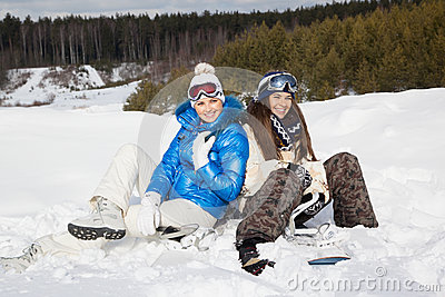 Two girls with snowboards sitting on the snow