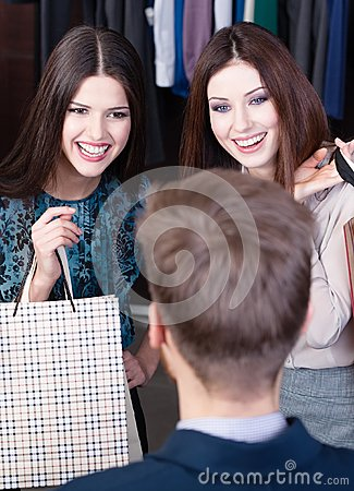 Two girls speak to salesperson