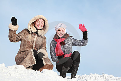 Two girls squatting on snow and waff one-arm